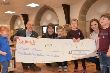 Children from Busy Bees nurseries  handover cheque to Fergus Crow, chief executive of Winston's Wish charity