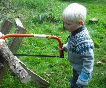 Children use real saws to chop wood. Credit: Elves and Fairies Woodland Nursery